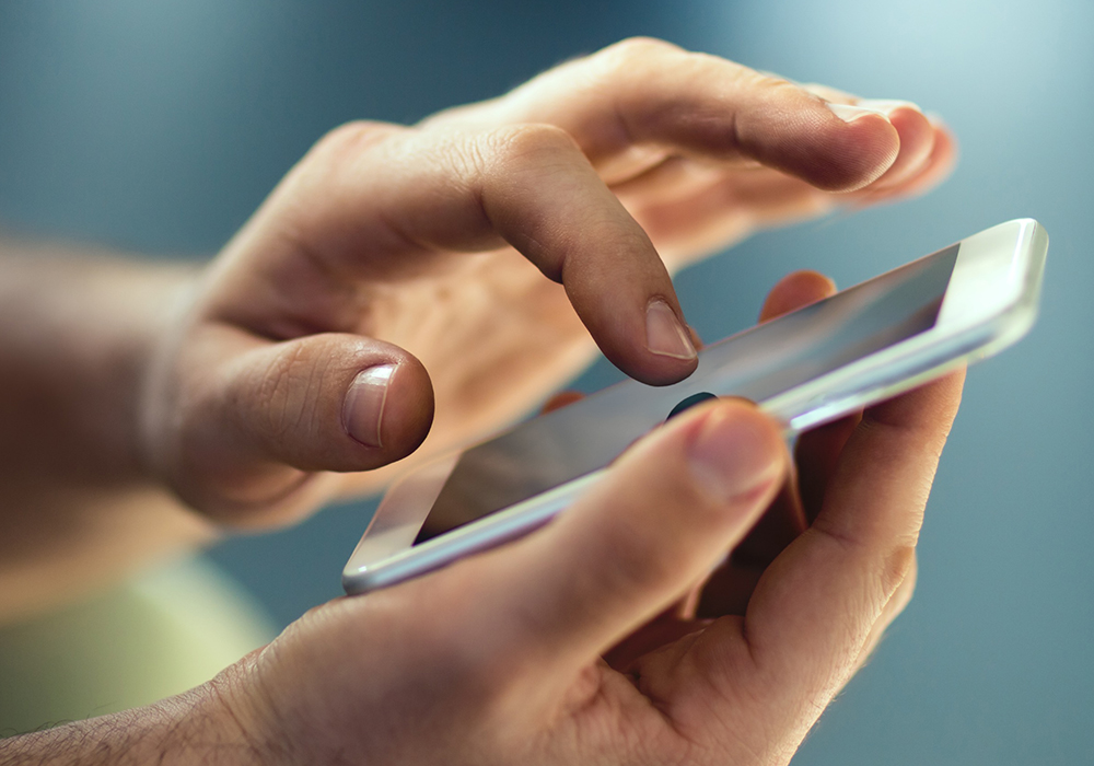 Hand holding a cellphone, while touching screen.